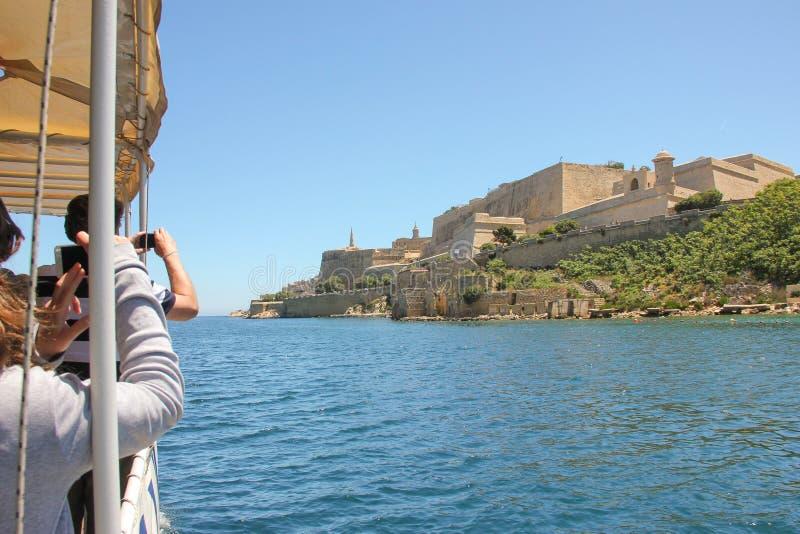 Los turistas en el barco viajan en el puerto magnífico que toma la foto de la vista más famosa de La Valeta, Malta imagen de archivo libre de regalías