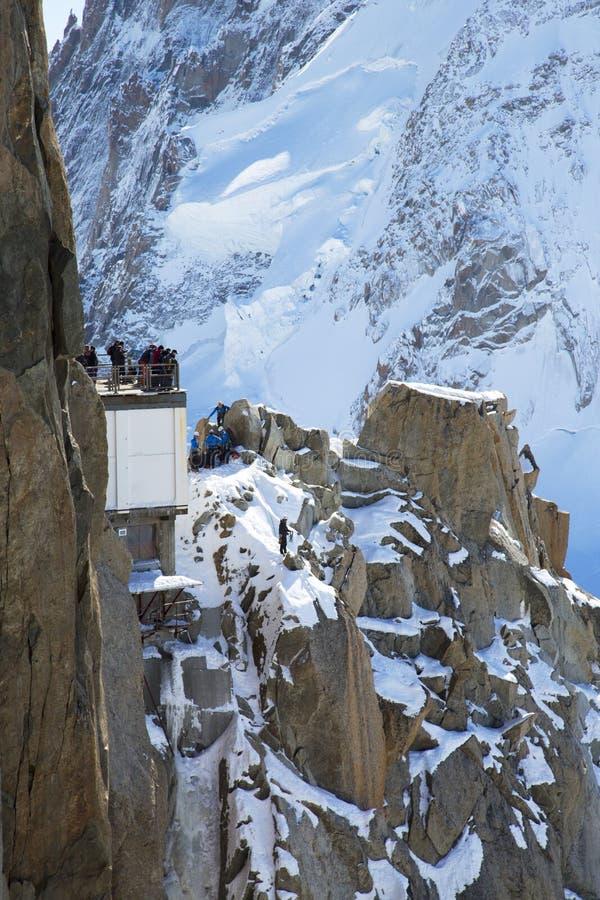 Los turistas en la montaña rematan la estación de Aiguille du Midi 3842 m en las montañas francesas que miran ejercicio de los esc fotos de archivo