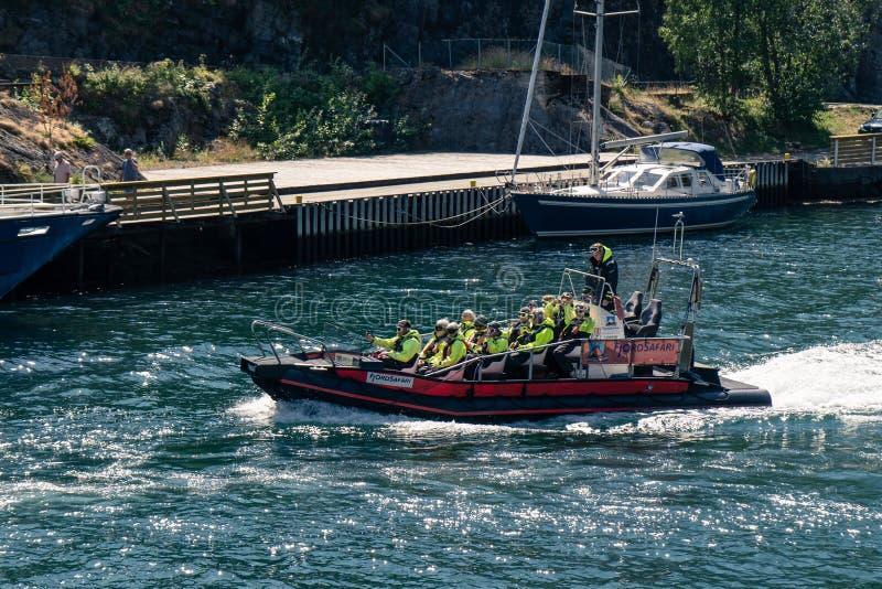 Los turistas en un safari del fiordo de Aurlandsfjord viajan en el puerto de Flam en un barco de la COSTILLA foto de archivo libre de regalías