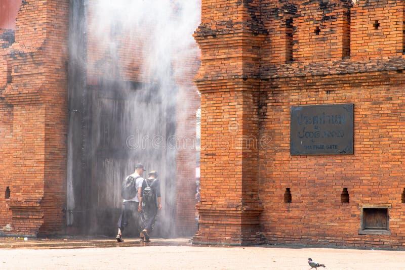 Los turistas están caminando a través del espray de agua instalado en la puerta de Thapae fotografía de archivo libre de regalías