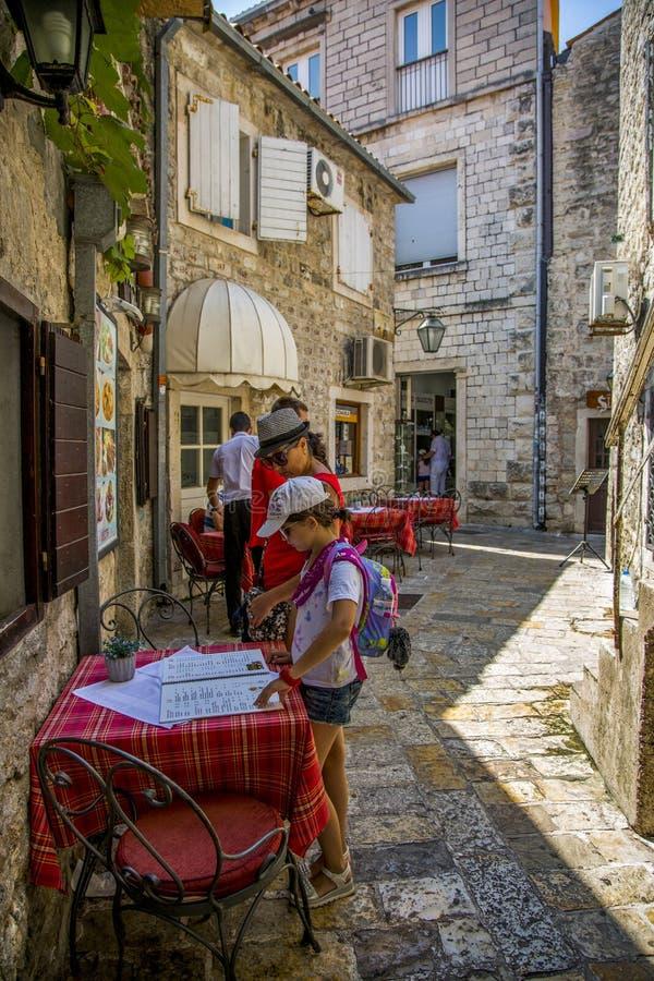 Los turistas están considerando el menú de un café al aire libre en la ciudad vieja fotos de archivo libres de regalías