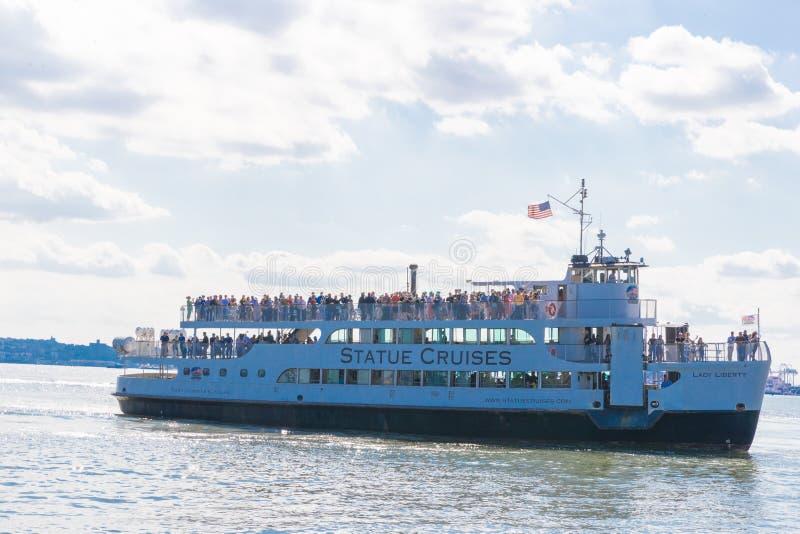 Los turistas están subiendo al barco de las travesías de la estatua fotos de archivo