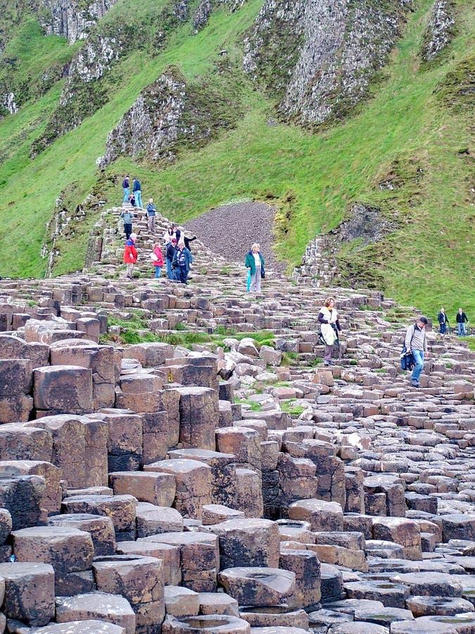 Los turistas exploran las formaciones de roca inusuales en el terraplén gigante del ` s imagenes de archivo