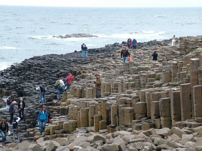Los turistas exploran las formaciones de roca inusuales en el terraplén gigante del ` s fotos de archivo
