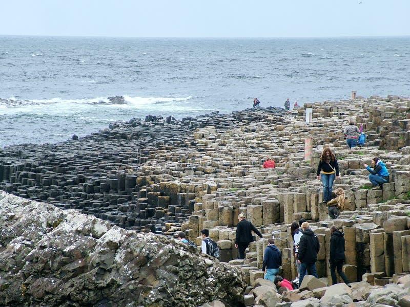 Los turistas exploran las formaciones de roca inusuales en el terraplén gigante del ` s imagen de archivo libre de regalías
