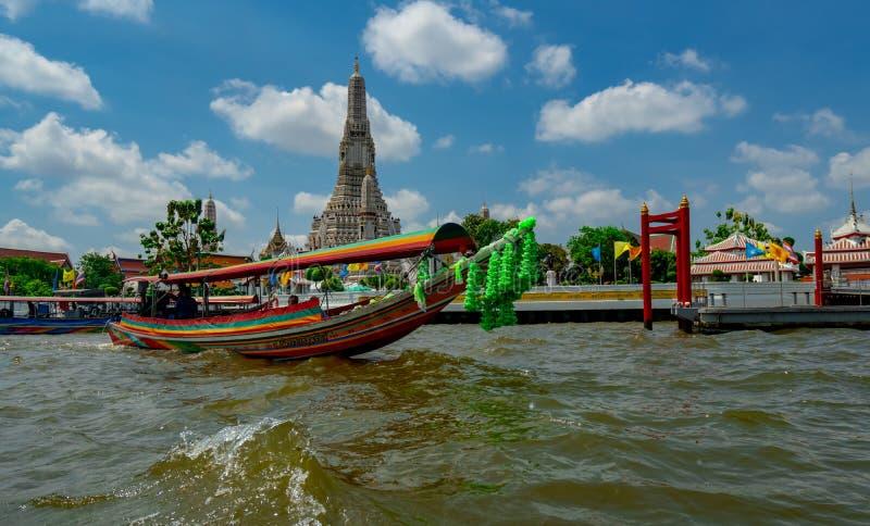 Los turistas extranjeros alquilan los barcos para mirar a Wat Arun Ratchawararam a lo largo del río Chao Phraya el día soleado co fotografía de archivo libre de regalías