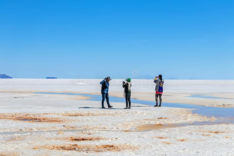 Los turistas felices disfrutan de actividades del viaje del jeep en los planos Salar de Uyuni de la sal en Bolivia imágenes de archivo libres de regalías