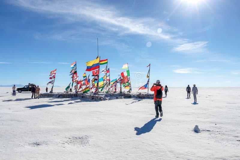 Los turistas felices disfrutan de actividades del viaje del jeep en los planos Salar de Uyuni de la sal en Bolivia imagenes de archivo