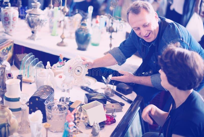 Los turistas felices estudian la gama de mercado de pulgas foto de archivo libre de regalías