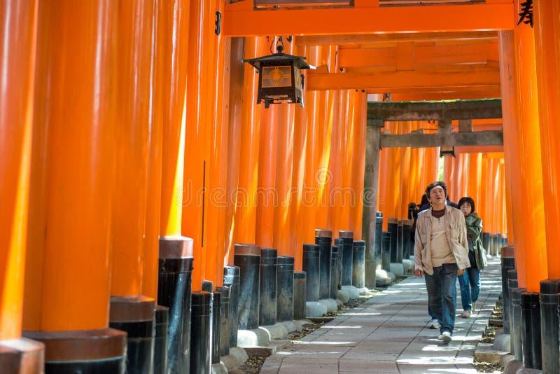 Los turistas japoneses exploran la capilla de Fushimi Inari Taisha fotos de archivo