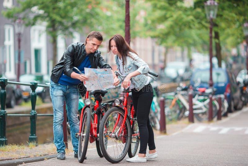 Los turistas jovenes juntan la mirada del mapa en ciudad europea Familia de dos el vacaciones en Amsterdam foto de archivo libre de regalías