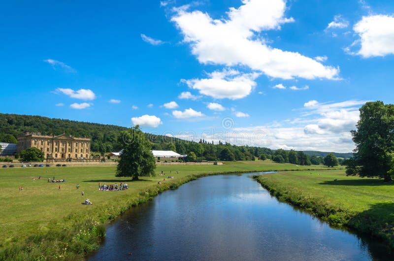 Los turistas meriendan en el campo en el río Derwent por la casa de Chatsworth en verano imágenes de archivo libres de regalías