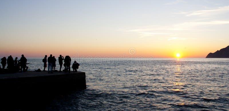 Los turistas miran la puesta del sol fotografía de archivo
