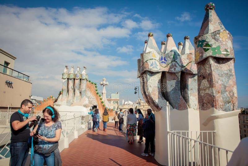 Los turistas miran las chimeneas coloridas en el tejado de la casa Batllo fotografía de archivo libre de regalías