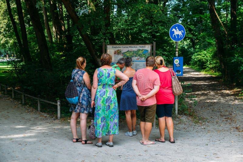 Los turistas miran un mapa en el jardín inglés, un parque famoso en el centro de Munich, Alemania imágenes de archivo libres de regalías