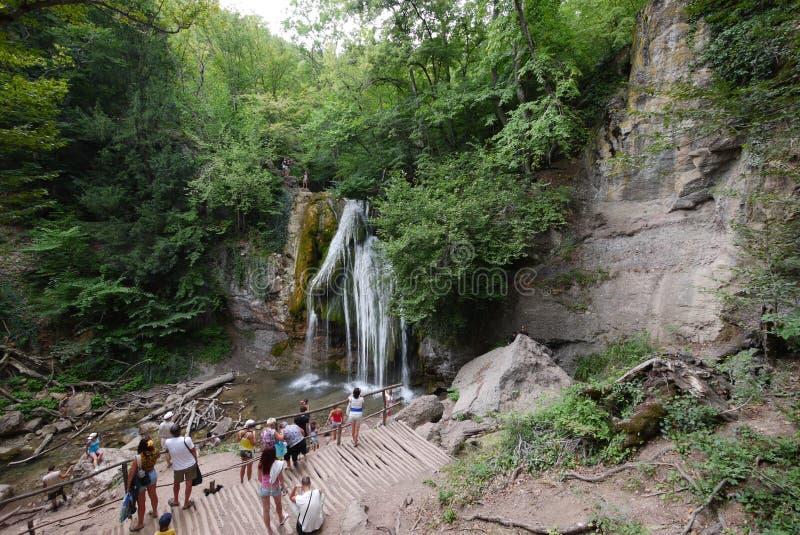 Los turistas miran y fotografían una cascada hermosa de la montaña en una plataforma de la visión cerca de la montaña rocosa fotos de archivo