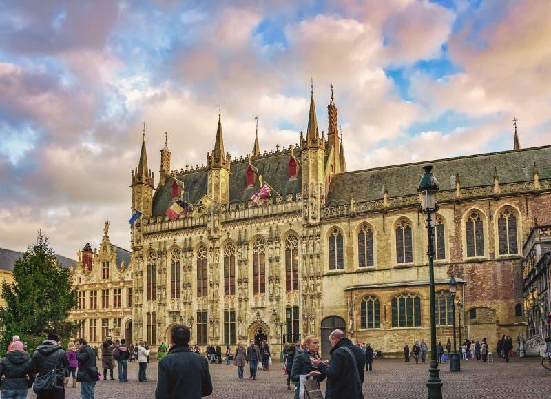 Los turistas no identificados acercan al ayuntamiento gótico en el cuadrado del Burg, Brujas, Bélgica imagenes de archivo