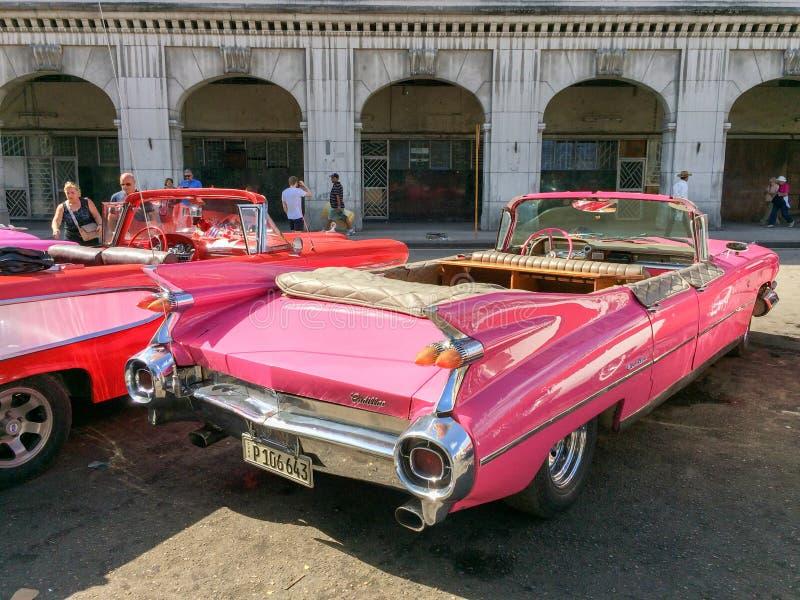 Los turistas que admiraban los coches clásicos americanos del vintage parquearon en La Habana, Cuba fotos de archivo libres de regalías