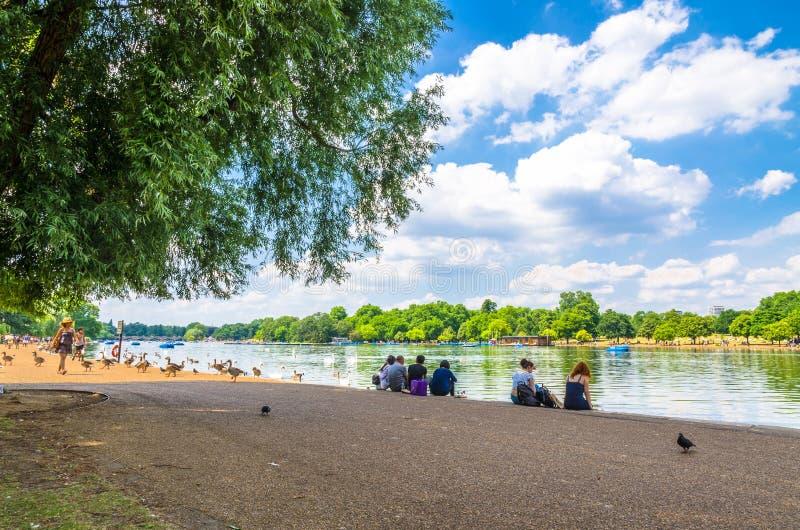 Los turistas que disfrutan del verano resisten en Hyde Park en Londres foto de archivo libre de regalías