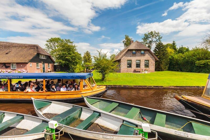 Los turistas que gozan de un canal cruzan con un barco de madera en el famou foto de archivo