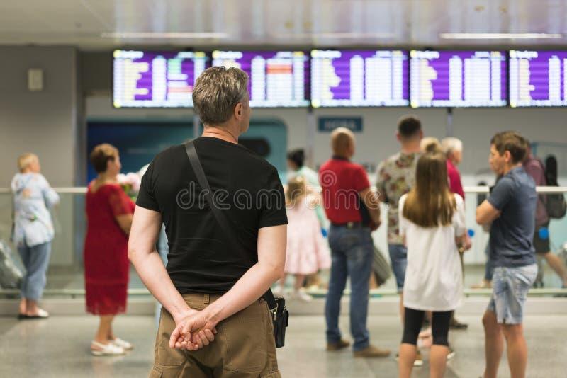 Los turistas se colocan delante de un tablero de la información dentro del aeropuerto Empañe la imagen de la gente que espera del fotos de archivo libres de regalías