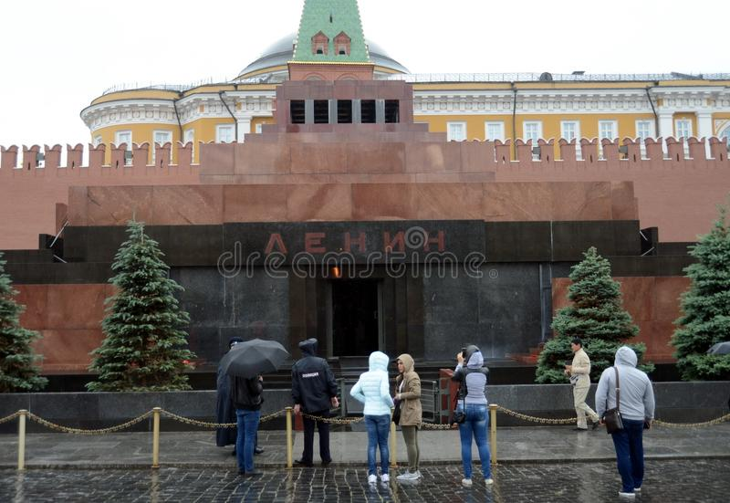 Los turistas se colocan en la lluvia en el mausoleo de Vladimir Lenin en Plaza Roja fotografía de archivo
