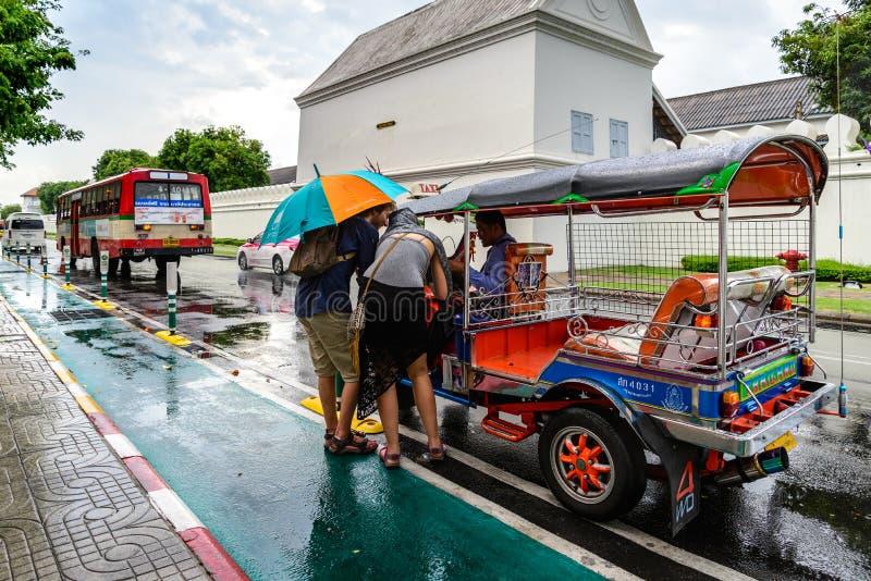 Los turistas toman el servicio de Tuk Tuk en el día lluvioso para el viaje el 2 de julio de 2015 en Bangkok, Tailandia fotos de archivo