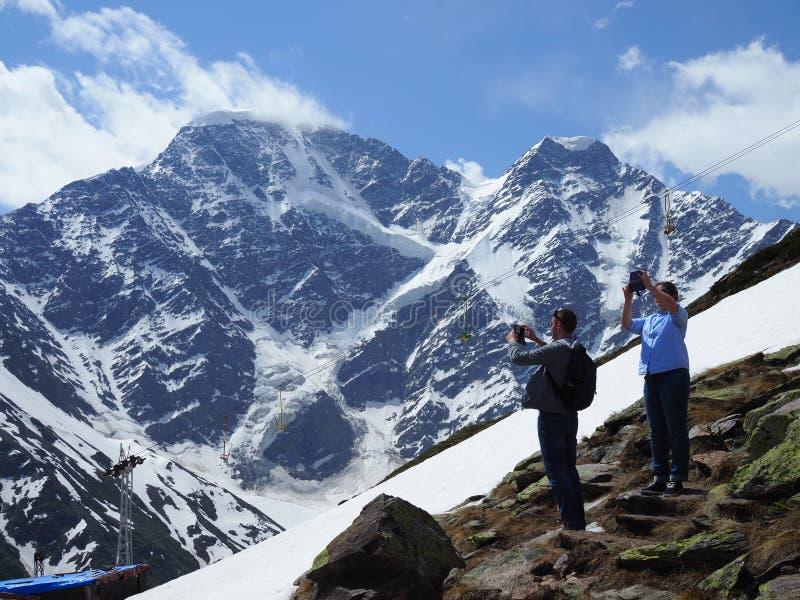 Los turistas toman imágenes en las hermosas vistas del teléfono altas en las montañas en un día soleado claro en el fondo del fam fotografía de archivo libre de regalías