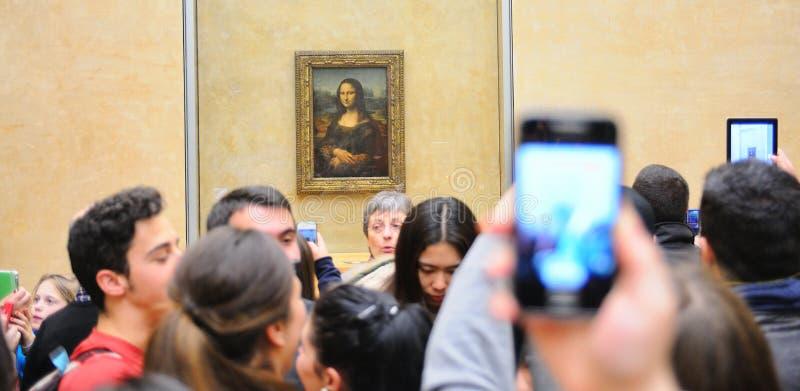 Los turistas toman a imágenes la pintura de Mona Lisa (Monna Lisa o La Gioconda en italiano y La Joconde en francés) en el museo  fotos de archivo