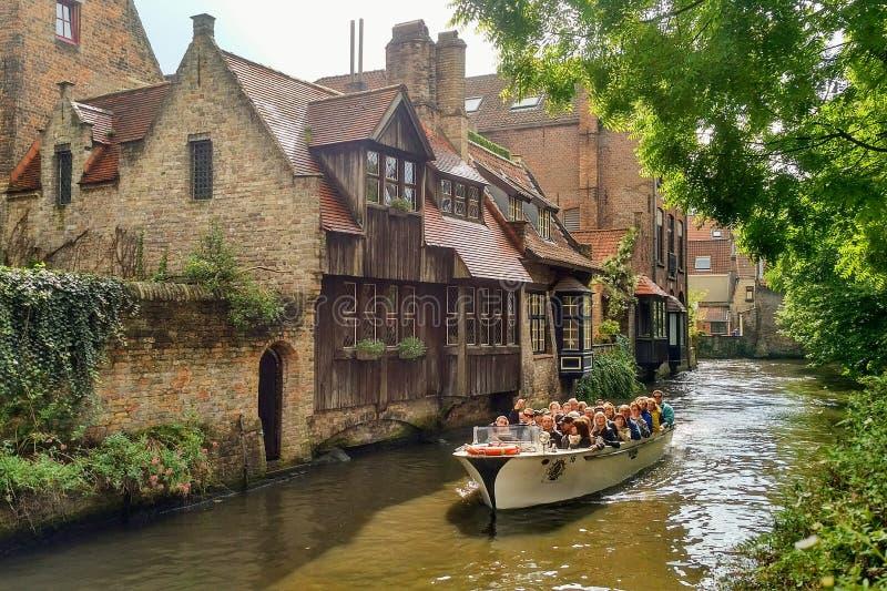 Los turistas toman un viaje escénico del barco en los canales de Brugges, Bélgica fotografía de archivo libre de regalías