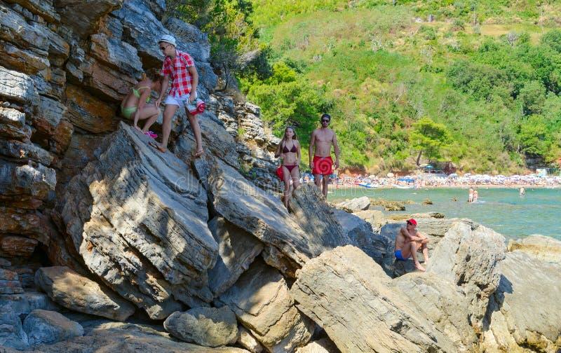 Los turistas van en rocas enormes de la playa de Mogren al acantilado con el punto de visión, Budva, Montenegro imagen de archivo libre de regalías