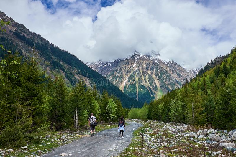 Los turistas van en un camino de la montaña del bosque fotos de archivo