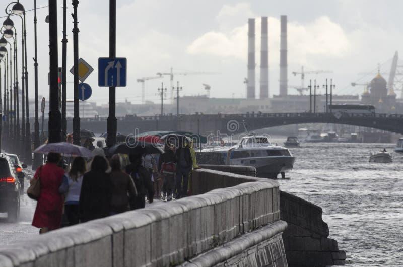 Los turistas y los visitantes durante una lluvia - gente no identificada de la ciudad que caminan fotografía de archivo libre de regalías