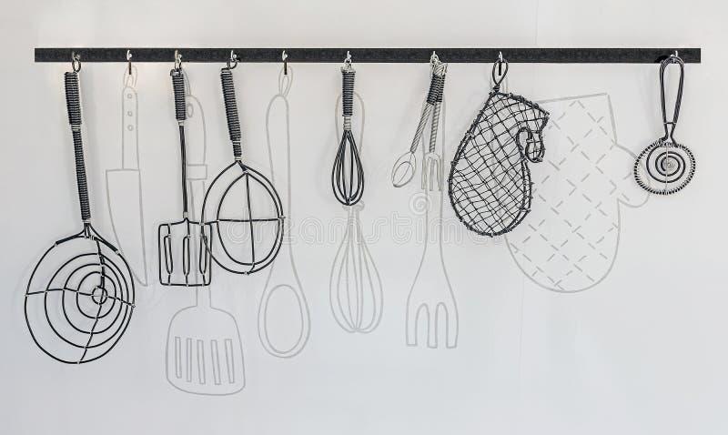 Los utensilios de la cocina del alambre cuelgan en la pared blanca fotos de archivo libres de regalías