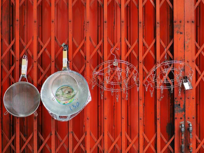Los utensilios de la cocina se cuelgan en las puertas metálicas del plegamiento retractable cerrado fotos de archivo