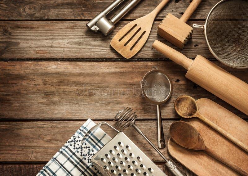 Los utensilios rurales de la cocina en vintage planked la tabla de madera fotografía de archivo
