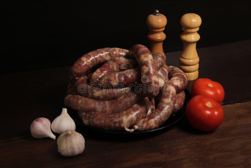 Los vínculos alemanes hechos en casa fragantes de la col de la salchicha con la máquina para picar carne ponen en una placa en la imagen de archivo libre de regalías