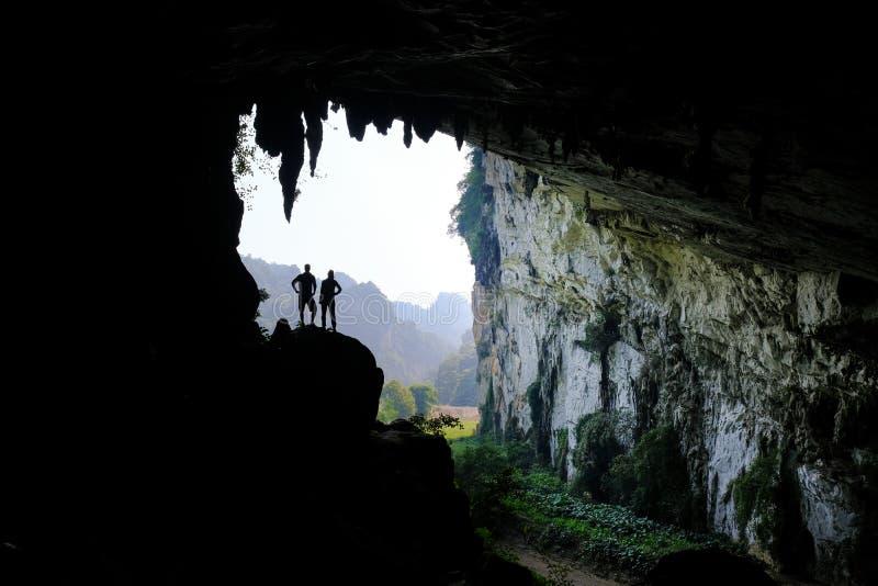 Los vagos sean lagos/Vietnam, 03/11/2017: Siluetas de dos personas que se colocan en un afloramiento rocoso dentro de una cueva g fotografía de archivo