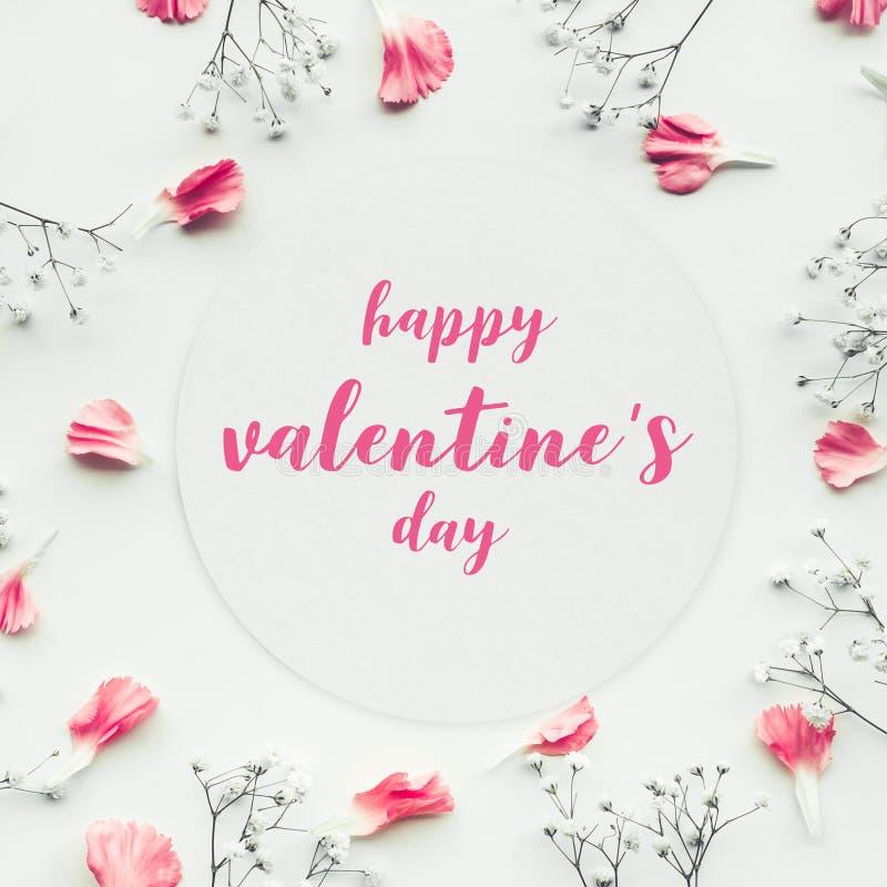 Los valentine's felices en tarjeta del Libro Blanco con el pétalo florecen imágenes de archivo libres de regalías