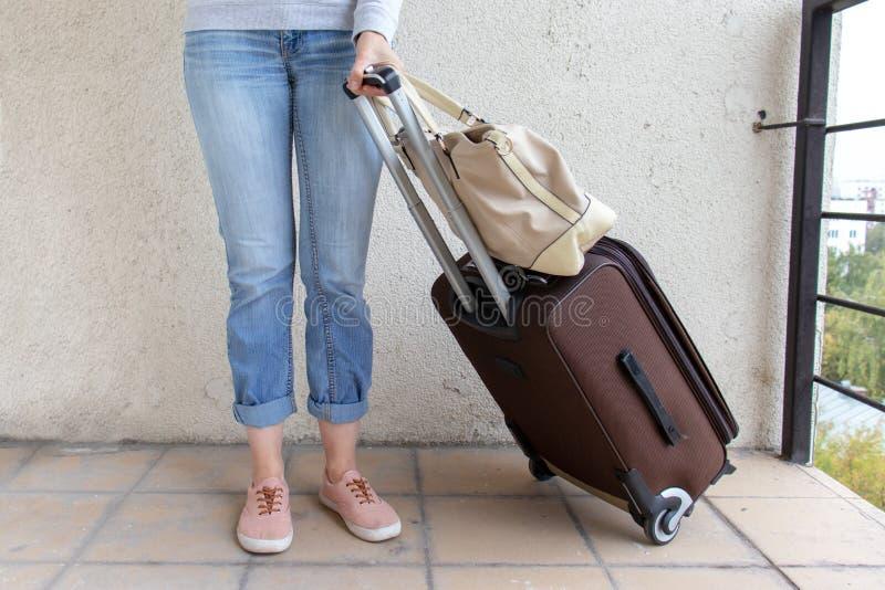 Los vaqueros que llevan de la mujer joven llevan un bolso del equipaje Concepto del viaje y de la relocalización imagen de archivo