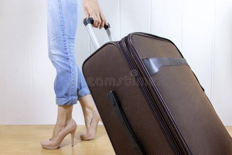 Los vaqueros que llevan de la mujer joven y las altas colinas llevan un bolso del equipaje Concepto del viaje y de la relocalizac fotos de archivo