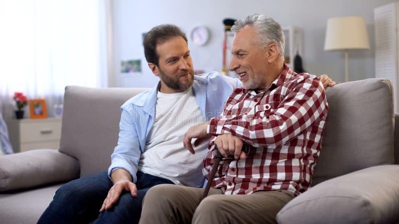 Los varones adultos alegres que comparten memorias engendran e hijo que bromea y que tiene buen tiempo imagenes de archivo