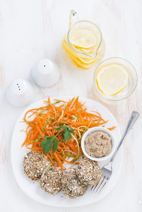 Los veganos almuerzan - las hamburguesas haba y ensalada de la zanahoria, visión superior imagen de archivo