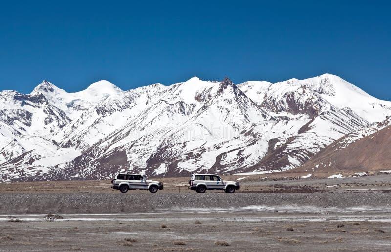 Los vehículos van en la manera de la montaña en la prefectura de Ngari, Tíbet occidental imagenes de archivo