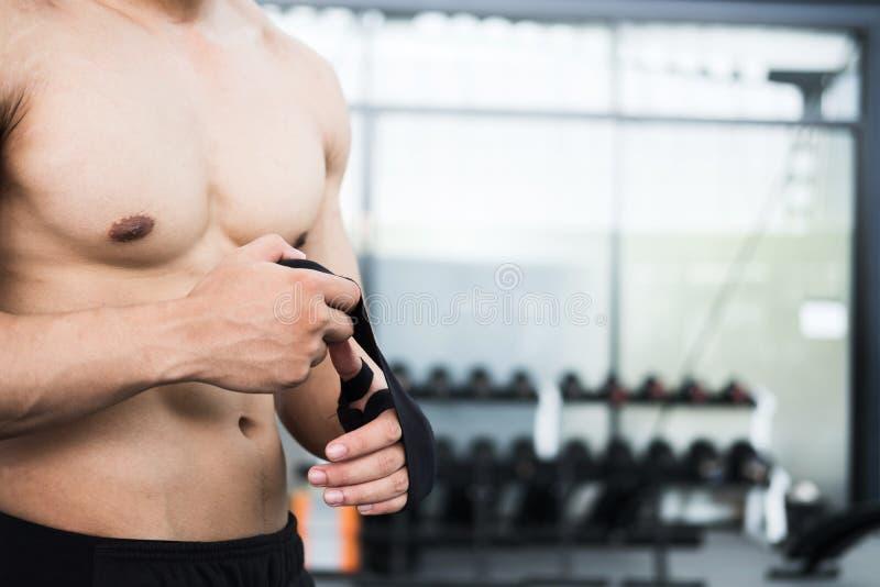 los vendajes masculinos del desgaste del combatiente en hombre muscular del puño atan el vendaje encendido imagen de archivo
