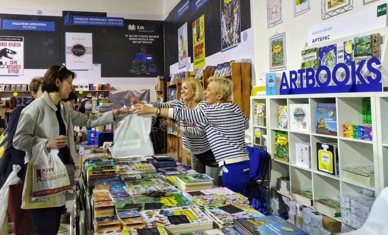 Los vendedores de libros dan a los compradores comprados los libros en la exposición del libro en museo del arsenal en Kiev imagen de archivo