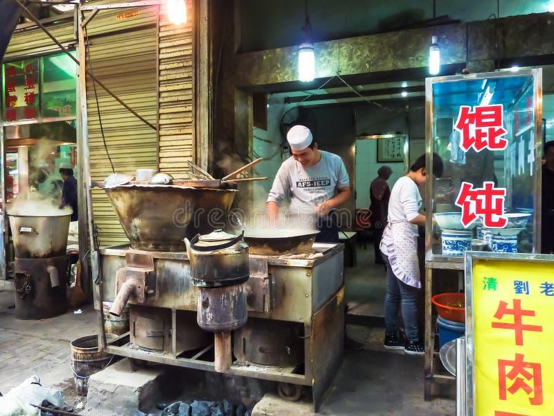 Los vendedores del mercado en la calle de Xian ofrecen a sus clientes diversos tipos de raviolis imagen de archivo