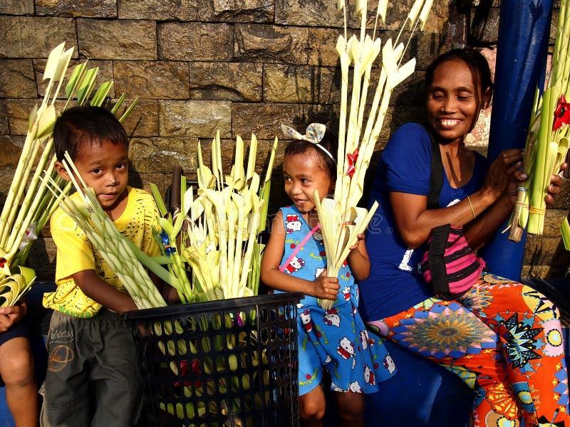 Los vendedores preparan hojas de palma para ser vendidos a los patrón de la iglesia con objeto de Ramos Domingo imagen de archivo libre de regalías