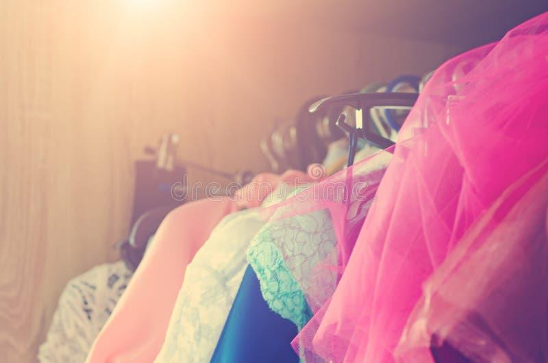 Los vestidos de las mujeres hermosas cuelgan en la suspensión en el armario Tono en el estilo de instagram fotos de archivo libres de regalías