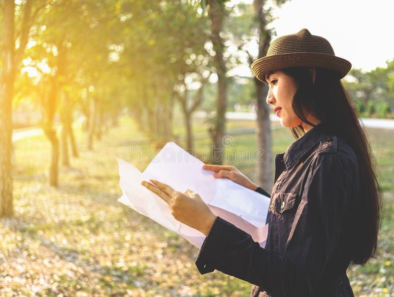 Los viajeros asiáticos de la mujer con hacer excursionismo, situación ven el mapa, planeamiento del viaje del concepto solament imagen de archivo